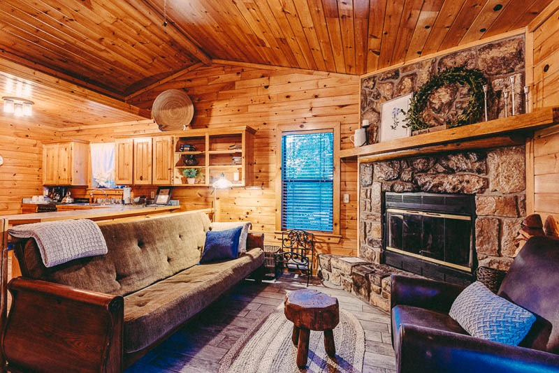 inside cabin with futon and wood fireplace