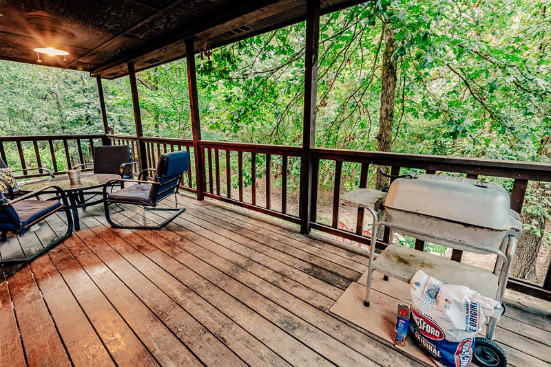 cabin back porch with seating and table plus charcoal grill
